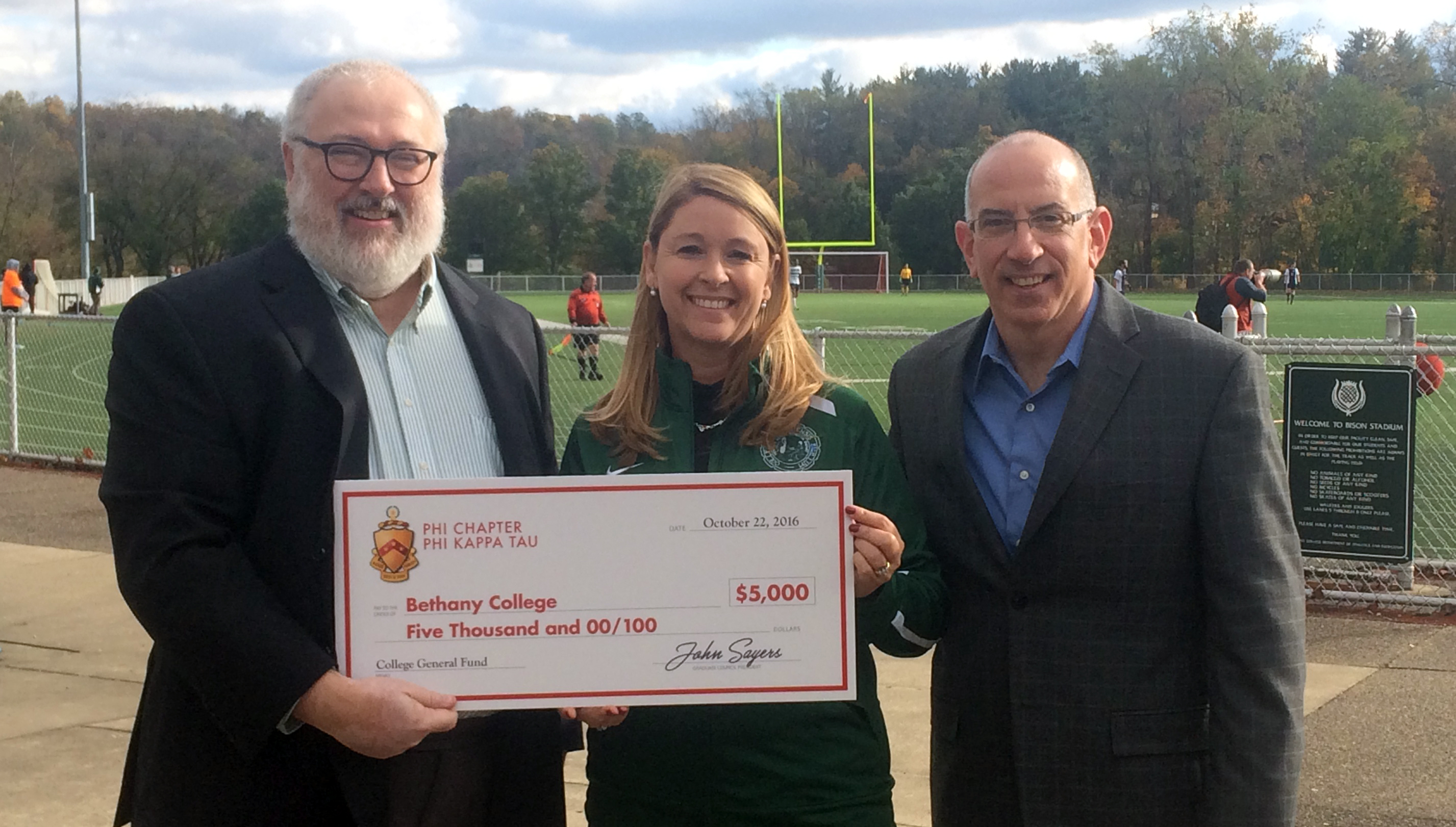 John Sayers (left) and Tom Skena present a check to Bethany President Tamara Rodenberg from Phi Chapter of Phi Kappa Tau to help in her new fundraising effort. Photo by Stephanie Gordon